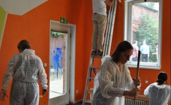 Symbolbild zum Thema Engagement von Unternehmen: Das Bild zeigt mehrere Personen in Kleidung zum Streichen von Wänden. Sie stehen auf Leitern und haben Pinsel, Rollen und andere Utensilien in der Hand.