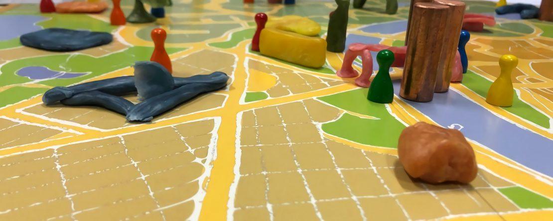 Das Bild zeigt ein Symbolbild zum Thema Organisationen, ein Spielbrett in Form einer Karte, mit verschiedenen Spielfiguren.