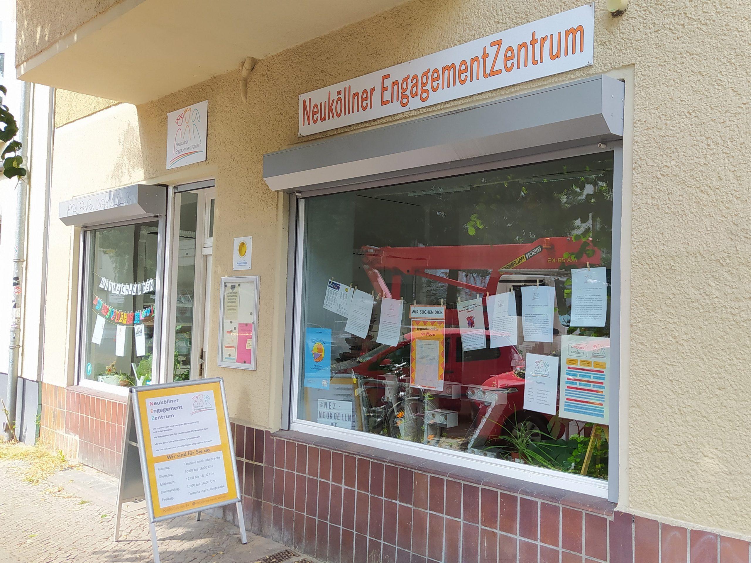 Das Bild zeigt die Außenansicht des Neuköllner EngagementZentrum: Ein Aufsteller neben der Eingangstür und das Schaufenster mit Engagement-Angeboten.
