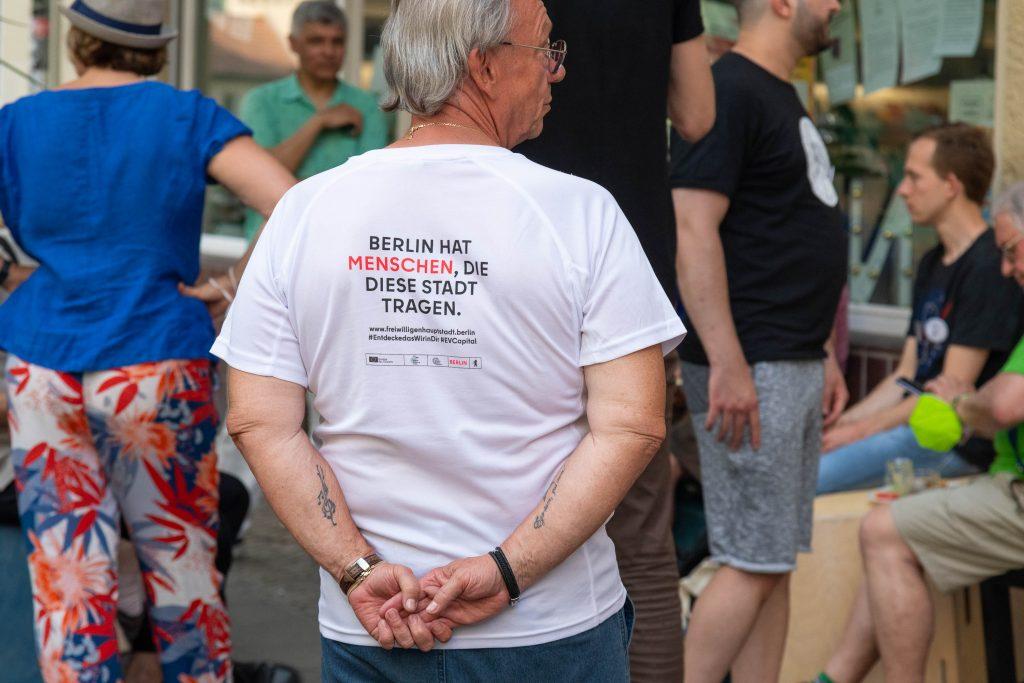"""Das Bild zeigt engagierte Personen vor dem Neuköllner EngagementZentrum. Auf einem T-Shirt steht geschrieben """"Berlin hat Menschen, die diese Stadt tragen."""""""