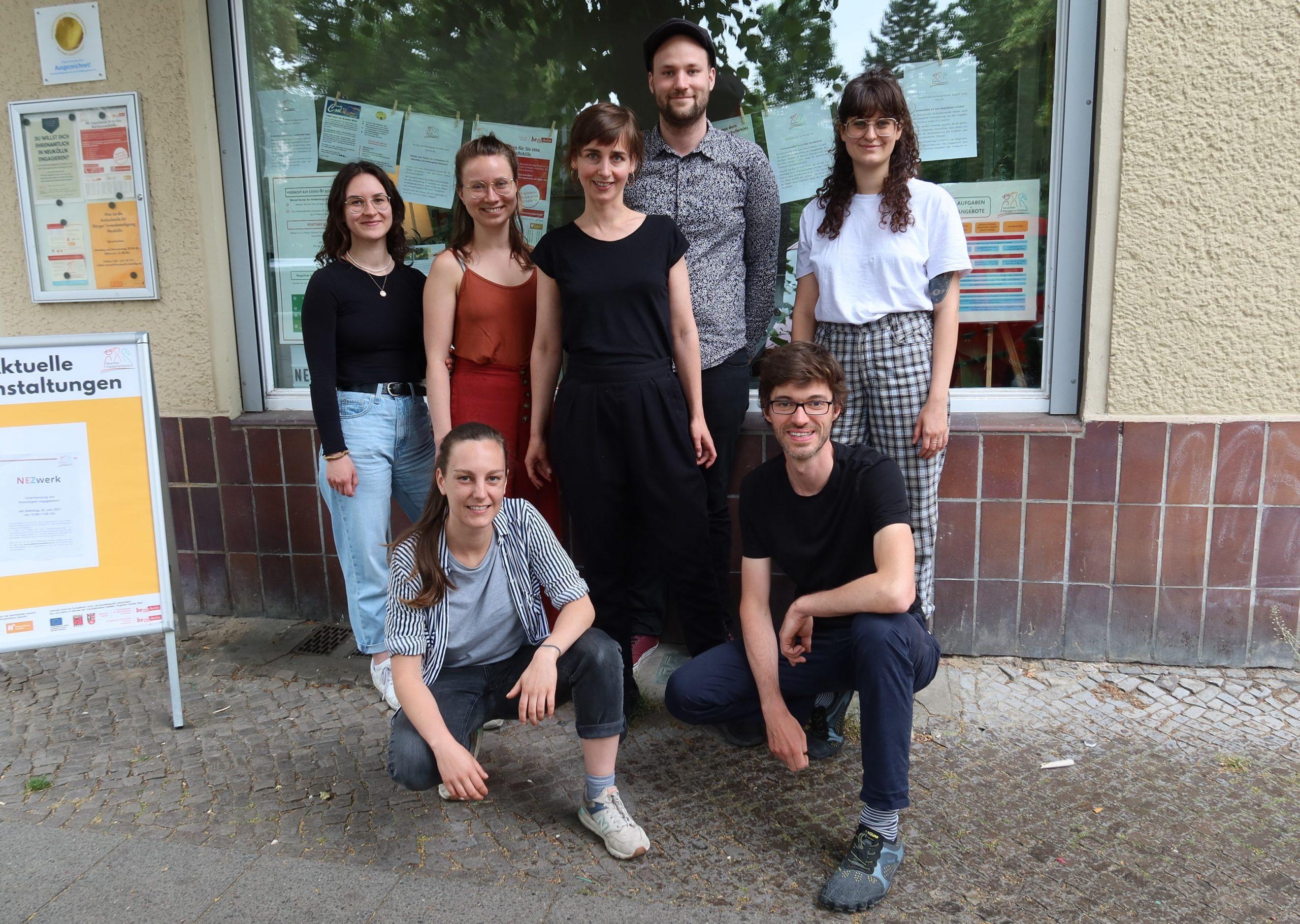 Das Bild zeigt sieben Personen des Teams des Neuköllner EngagementZentrums (NEZ) vor dem Schaufenster des NEZ.